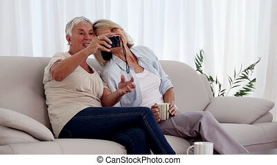 Mature women taking a picture together on the couch in the...
