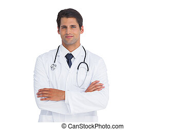 Attractive doctor smiling with arms crossed on white...