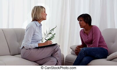 Therapist helping her patient sitting on sofa