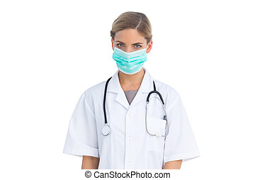 Serious nurse wearing surgical mask - Standing serious nurse...