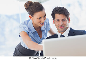 Happy business people looking together at the laptop in the...