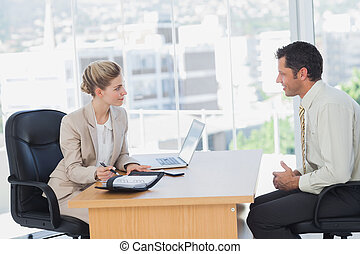 Smiling businesswoman interviewing businessman in the office