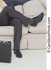 Businessman with legs crossed on couch in office