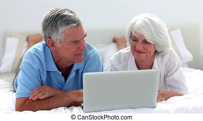 Mature couple using laptop together on bed at home