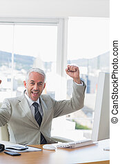 Businessman cheering at his desk in the office