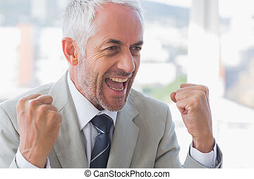 Successful businessman cheering and clenching fists