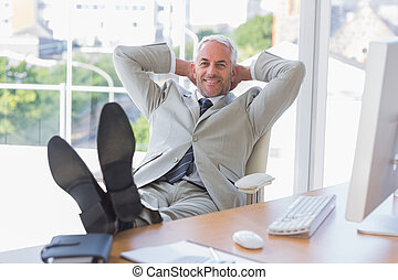Businessman relaxing at desk and smiling at camera in his...