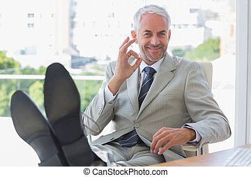 Smiling businessman giving ok sign at hs desk in office