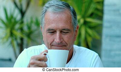 Retired man enjoying coffee outside in slow motion