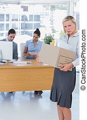 Forlorn businesswoman leaving office after being let go