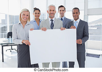 Business team holding large blank poster and smiling at...