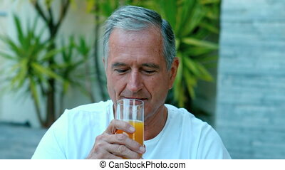 Retired man drinking orange juice outside in slow motion