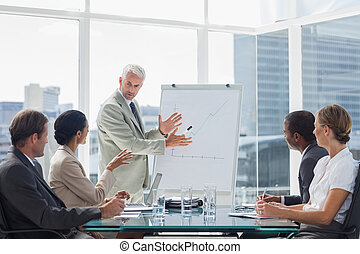 Businessman in front of a growing chart during a meeting...