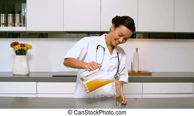 Home nurse pouring glass of orange juice in kitchen in slow...