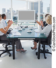 Business people applauding during a video conference while...