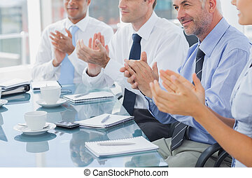 Group of business people clapping together during a meeting