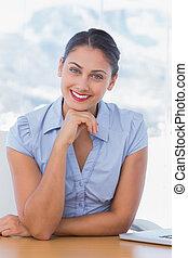Cheerful businesswoman sitting at her desk