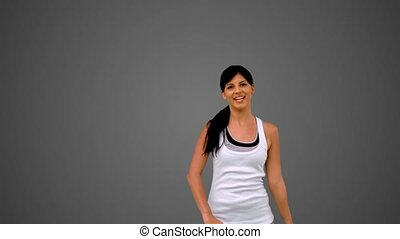 Fit brunette stretching and waving on grey background in...