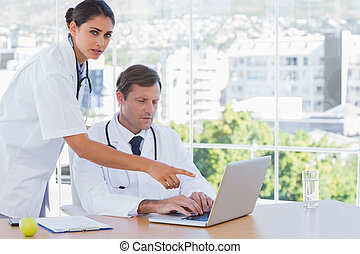 Doctor pointing at the laptop of a colleague