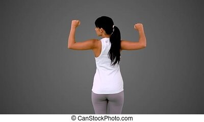 Fit brunette tensing her arms muscles on grey background in...