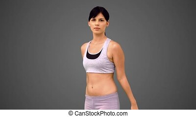 Fit brunette making martial arts pose on grey background in...