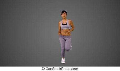 Attractive brunette jogging on grey background in slow...