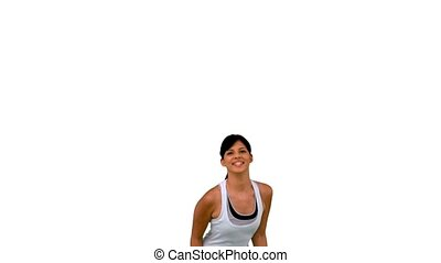 Fit woman jumping up on white background in slow motion