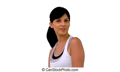 Fit woman tossing her hair and smiling at camera on white...