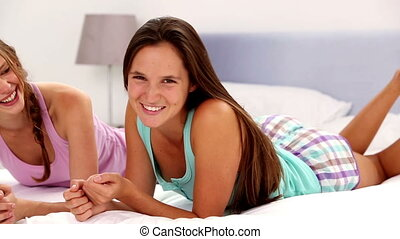 Girls embracing and smiling at camera lying on bed