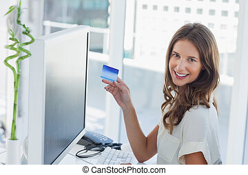 Cheerful brunette designer purchasing online with her credit...