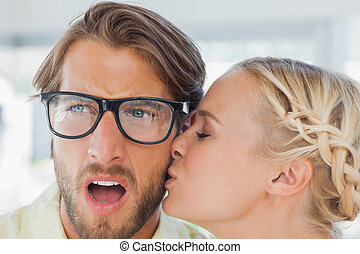 Attractive designer kissing her colleague in the office