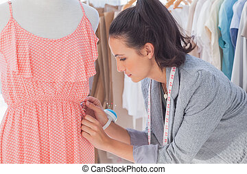 Creative designer adjusting dress on a mannequin