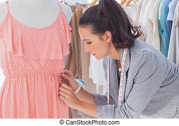 Creative designer adjusting dress on a mannequin