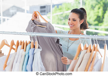 Fashion woman choosing dress in a studio