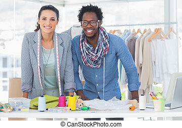 Two fashion designers smiling and looking at camera