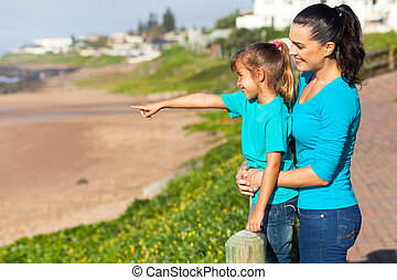 daughter pointing at ocean with mother at the beach
