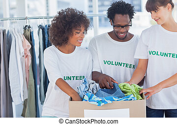 Cheerful volunteers taking out clothes from a donation box...