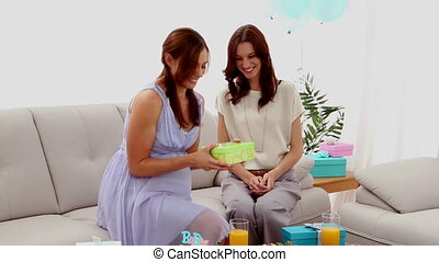Expectant mother receiving present from friend at home at...