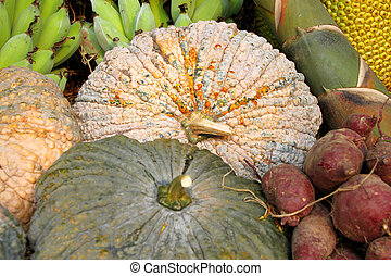 Pumpkin among pile of tropical fruits on local market