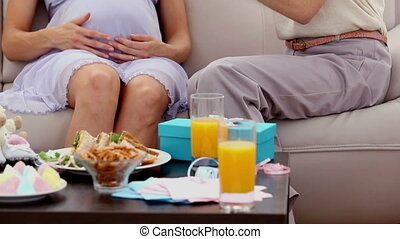 Expectant mother getting a present from friend on sofa at...