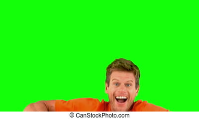 Handsome man jumping on green screen in slow motion