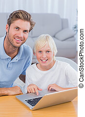 Father using laptop with his son in the living room