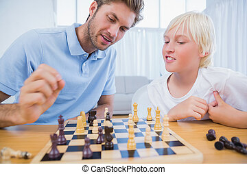 Father and his son playing chess together in the living room