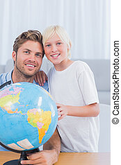 Father and his little boy looking at globe in the living...