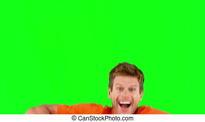 Attractive man jumping in front of the camera on green...