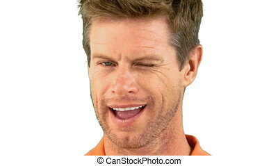 Cheerful man winking an eye on white background in slow...
