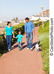 young couple with their daughter walking pet dog