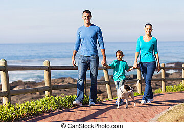 young family walking their dog at the beach