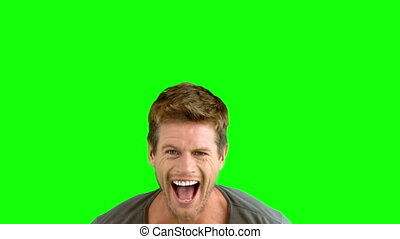 Handsome man laughing on green scre