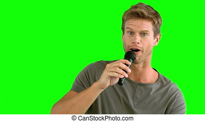 Man with microphone singing on green screen in slow motion